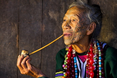 Myanmar, Mindat. A Chin lady with traditional tattoed face, enjoying her pipe.