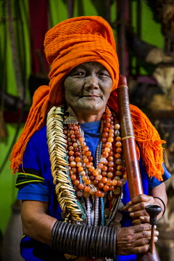 MYA2224 Myanmar, Mindat. A Chin lady with traditional tattoed face, clutching a large pipe.