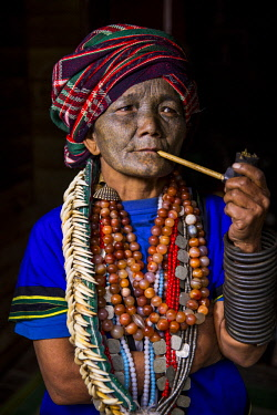 MYA2230 Myanmar, Mindat. A Chin lady with traditional tattoed face, smoking her pipe.
