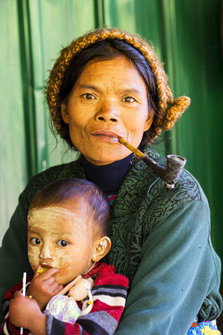 MYA2213 Myanmar, Mindat. A Chin lady with her child, smoking a pipe on her verandah.