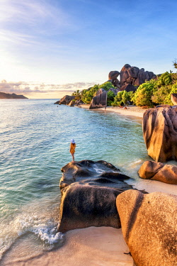 CLKAC93278 A young woman admires the sunset at Anse Source d'Argent, La Digue, Seychelles, Africa (MR)