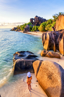 CLKAC93279 A young woman admires the sunset at Anse Source d'Argent, La Digue, Seychelles, Africa (MR)