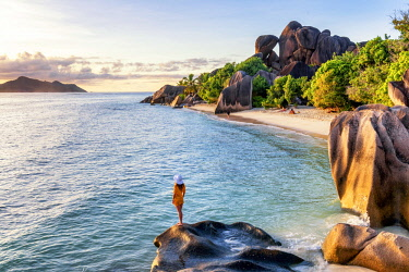 CLKAC93281 A young woman admires the sunset at Anse Source d'Argent, La Digue, Seychelles, Africa (MR)