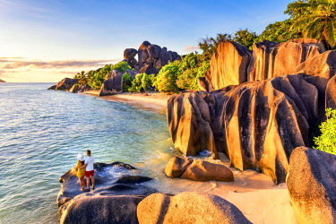 CLKAC93282 A young couple admires the sunset at Anse Source d'Argent, La Digue, Seychelles, Africa (MR)