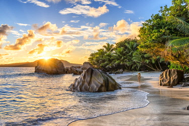 CLKAC93308 A young woman enjoys the sunrise on Anse Patates beach. La Digue, Seychelles, Africa (MR)