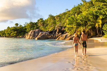 CLKAC93359 A beautiful couple walking along Anse Lazio beach at sunset. Praslin island, Seychelles, Africa