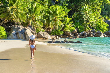 CLKAC93395 Beautiful woman strolling along Anse Georgette beach. Praslin island, Seychelles, Africa (MR)