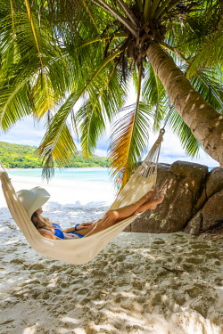CLKAC93435 A young woman relaxing on a hammock. Anse Lazio beach, Praslin island, Seychelles, Africa (MR)