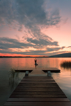 CLKGA93545 Woman dancing on a Wood pier on Pusiano lake at sunset, Bosisio Parini, Lecco province, Lombardy, italy