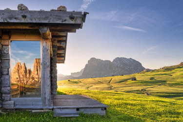 CLKMK93202 Alpe di Siusi/Seiser Alm, Dolomites, South Tyrol, Italy. Sunrise on the Alpe di Siusi/Seiser Alm. The peaks of the Sciliar are reflected in a glass pane