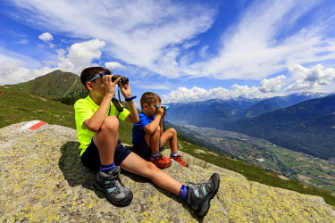 CLKRM94082 Two children sit on rocks look towards Morbegno with binoculars, Alpe Bassetta, Valtellina, Sondrio, Lombardy, Italy