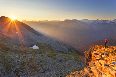 CLKDC94343 Hiker observes the sunrise from the summit of Petersköpfl, Zillertal Alps, Tyrol, Schwaz district, Austria. (MR)