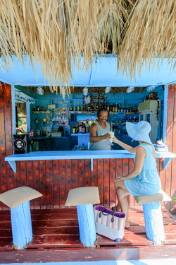 CLKRM94575 Barman serving a cocktail to a woman with hat, Long Bay, Antigua, Antigua and Barbuda, Caribbean, Leeward Islands, West Indies (MR)