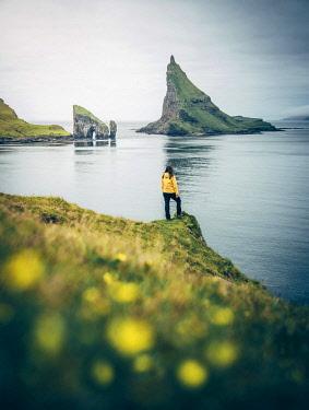 DEN0385AW Girl admiring Drangarnir and Tindholmur Faroe Islands, Europe