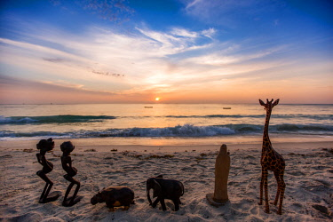 KEN11346 Kenya, Diani, Diani Beach, AfroChic, wooden carvings for sale on the beach with sea beyond at sunset.