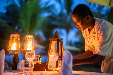 KEN11367 Kenya, Diani, Diani Beach, AfroChic, waiter lights candles and prepares the dining tables.