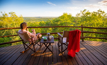 TZ3735 Tarangire Treetops, Tanzania, Elewana Collection, a guest relaxes with morning coffee on the deck outside his treetop room.