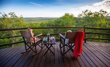 TZ3736 Tarangire Treetops, Tanzania, Elewana Collection, two children sit in rocking chairs with hot chocolate on the deck of their room.