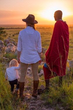 TZ3747 Tarangire Treetops, Tanzania, Elewana Collection, a Maasai scout, guest and child enjoy the view and last rays of sun on Sunset Hill.