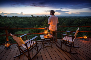 TZ3764 Tarangire Treetops, Tanzania, Elewana Collection, a man stands on the deck outside his room, sundowner drinks are set out.
