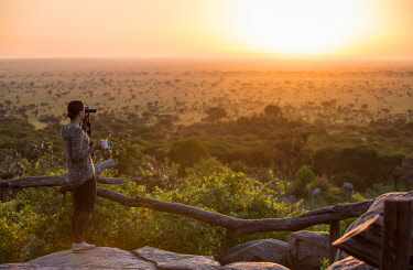 TZ3819 Pioneer Camp, Serengeti, Tanzania, Elewana Collection, a woman looks out over the Serengeti with binoculars and a coffee at sunrise.