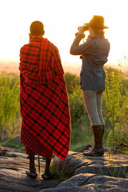 TZ3850 Pioneer Camp, Serengeti, Tanzania, Elewana Collection, a Maasai stands with a guest in the early morning as they scout the landscape for game.