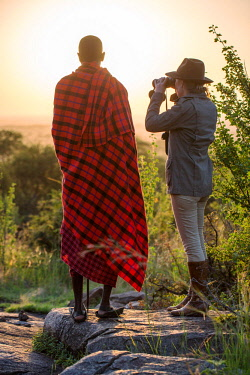 TZ3851 Pioneer Camp, Serengeti, Tanzania, Elewana Collection, a Maasai stands with a guest in the early morning as they scout the landscape for game.