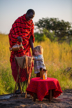 TZ3852 Pioneer Camp, Serengeti, Tanzania, Elewana Collection, a Maasai helps a little boy guest to wash his hands before a bush breakfast.