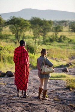 TZ3853 Pioneer Camp, Serengeti, Tanzania, Elewana Collection, a Maasai stands with a guest in the early morning as they scout the landscape for game.