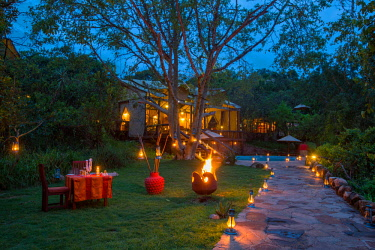 TZ3867 Tanzania, Serengeti, Migration Camp, Elewana, the lounge area, pool and pathway are lit in the evening, a table is set for supper on the lawn.