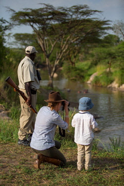 TZ3887 Tanzania, Serengeti, Migration Camp, Elewana, a guide points out hippo and birds to a mother and son on a stop on a game drive.