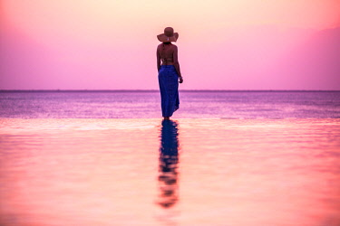 TZ3926 Tanzania, Zanzibar, Kilindi, Elewana Collection, a woman tourist stands on the infinity pool edge and watches the sunset over the sea.
