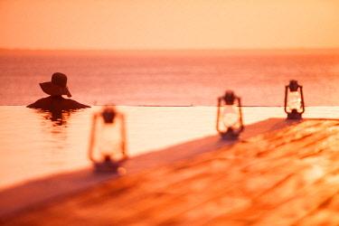 TZ3942 Tanzania, Zanzibar, Kilindi, Elewana Collection, a woman tourist relaxes in the main swimming pool, enjoying the sea view at sunset.
