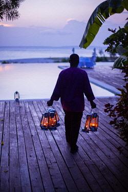 TZ3946 Tanzania, Zanzibar, Kilindi, Elewana Collection, a waiter arranges lanterns around the pool at dusk in preparation for evening alfresco dining.