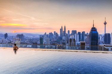 MAY0284AW Man in a infinity pool overlooking Kuala Lumpur skyline, Malaysia