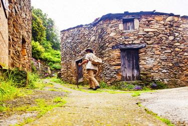 FRA10860 France, Occitane, Saint Gervais sur Mare. Pilgrim of Santiago de Compostela walking passing through the old hamlet of Mecle towards Santiago de Compostela on the Via Tolosana. MR