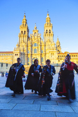 SPA8626 Spain, Galicia, Santiago de Compostela. Atuna singers walking in their Galician atire in front of the majestic Cathedral of Santiago de Compostela.