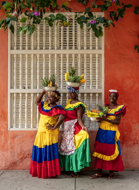 COL0518AW Colourful Palenqueras selling fruits on the street of Cartagena, Bolivar Department, Colombia (MR)