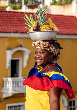 COL0520AW Colourful Palenquera selling fruits on the walls of Cartagena, Bolivar Department, Colombia (MR)