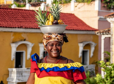 COL0521AW Colourful Palenquera selling fruits on the walls of Cartagena, Bolivar Department, Colombia (MR)