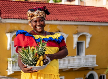 COL0522AW Colourful Palenquera selling fruits on the walls of Cartagena, Bolivar Department, Colombia (MR)