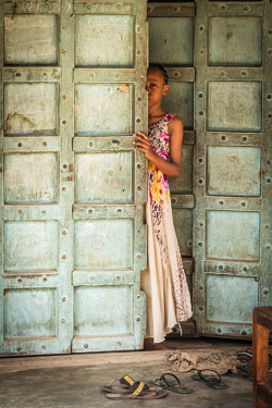 TZ4064AW Africa, Tanzania, Pangani. A girl in a traditional handmade door.