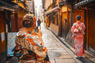 Kyoto, Kyoto prefecture, Kansai region, Japan. Tourists in kimono taking pictures with smartphone in Gion district.