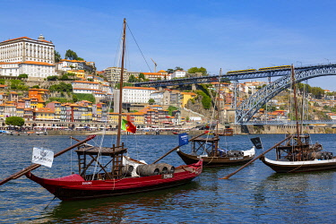 POR10091AWRF Traditional Rabelo boat designed to carry wine down Douro river with city skyline behind, Porto, Portugal