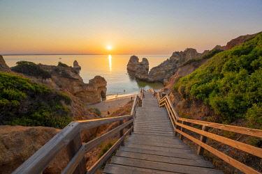 POR10101AW Portugal, Algarve, Faro district, Lagos, Camilo Beach (Praia do Camilo). Walkway to the beach at sunrise.