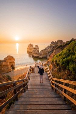 POR10102AW Portugal, Algarve, Faro district, Lagos, Camilo Beach (Praia do Camilo). Tourist with hat admiring the view at sunrise