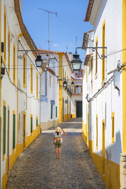POR10104AW Portugal, Alentejo, Evora. Woman looking at houses in a typical street