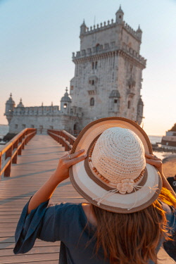 POR10108AW Portugal, Distrito de Lisboa, Lisbon, Belem Tower. Girl with hat admiring the view and Tejo river (MR)