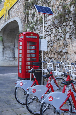 GB01113 Gibraltar, Gibraltar, British red telephone box and hire bikes by Southport Gates on Line Wall road