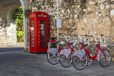 GB01124 Gibraltar, Gibraltar, British red telephone box and hire bikes by Southport Gates on Line Wall road